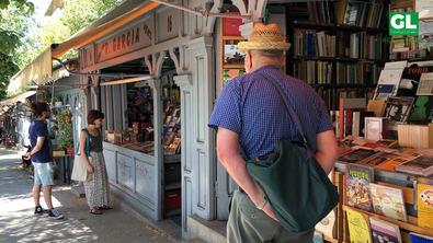 Madrileños y visitantes ojean libros en la Cuesta de Moyano.