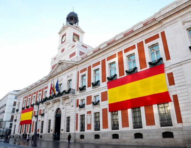 La fachada de la Real Casa de Correos luce dos banderas en honor a la Constitución.